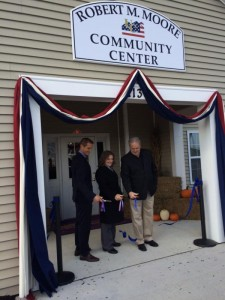 Tom Pollock, Matt Haydinger, and Anita Moore cut the ribbon on the solar electric system at United Communities, Joint Base McGuire-Dix-Lakehurst while dedicating the community center Robert M. Moore.